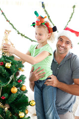 Father helping his daughter to put an angel on Christmas tree