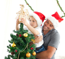Father helping his son to put an angel on the Christmas tree