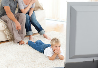 Attentive little boy watching television lying on the floor