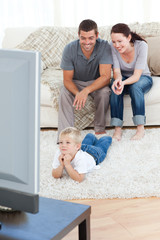 Cute little boy watching television on the floor with his parent