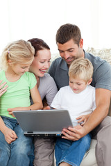 Adorable family working together on a laptop sitting on the sofa