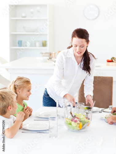 Adorable mother serving salad to her children for lunch
