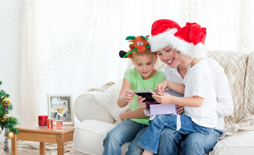 Mother and children looking at a calendar sitting on the sofa