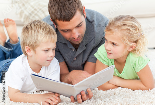 Children with father reading book in the carpet