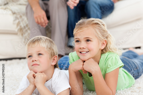 Brother and sister watching television on the floor with their p