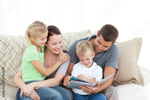 Adorable father and son reading a book to their family