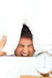 Man stressed by his alarm clock putting his head under the pillo