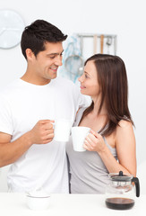 Adorable couple holding cups of coffee and looking at each other