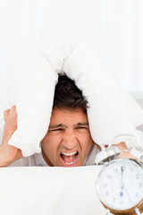 Unhappy man screaming while his alarm clock ringing