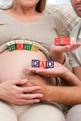 Close up of future parents holding cubes forming the words mom ,