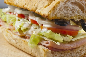 a sandwich with meat, vegetables and olives