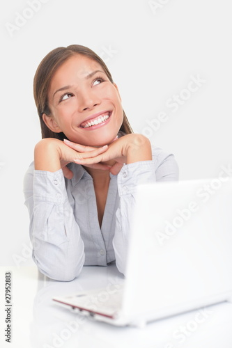 Happy woman thinking with computer
