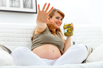 Embarrassed pregnant woman sitting on sofa with jar of pickles