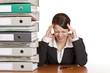 Frau im Büro hat Migräne / Kopfschmerzen durch zuviel Stress
