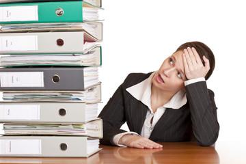 Frustrierte Frau im Büro schaut ungläubig Aktenstapel an