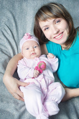 smiling mother with baby daughter in pink crawlers and rattle