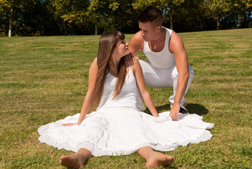 young couple happy sitting on grass white love relationship