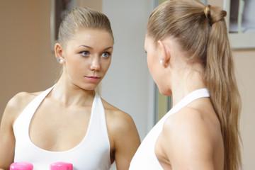 Beutiful blonde girl looking in mirror fitness gym
