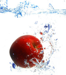 red apple under water with a trail of transparent bubbles..
