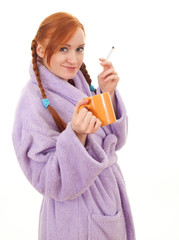 smoking young woman in bathrobe with big cup