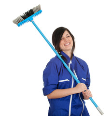 smiling woman in blue c overalls with sweeping brush