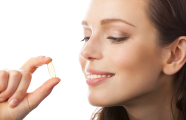 Portrait of woman with Omega 3 fish oil capsule, isolated