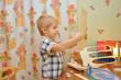 Постер, плакат: Маленький мальчик собирает модель парусника