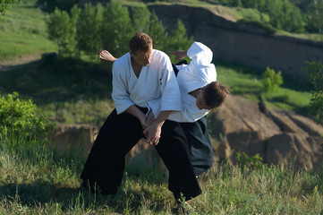 Two young man are training in Aikido in wood