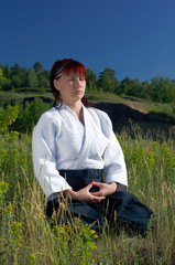 Young girl meditates after employment of an aikido
