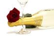 eine rote rose auf einer flasche sekt hinter einem sektglas