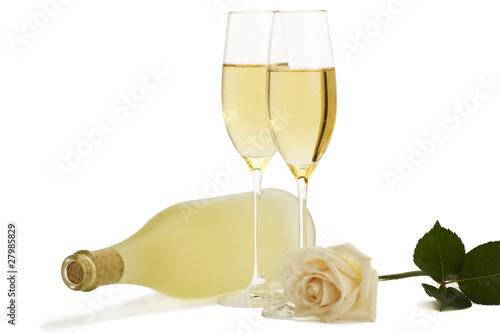 cremefarbene rose mit sektgläsern und liegenden flasche prosecco