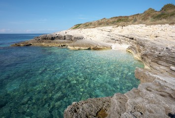 Empty rocky beach with clear turquoise water bay