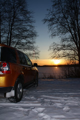 Car by frozen lake at sunset