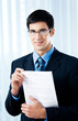 Happy businessman showing document or contract, at office