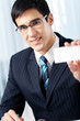 Smiling businessman giving business card, at office
