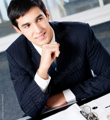 Portrait of thinkihg businessman with documents at office