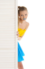 Young woman looks out because of door