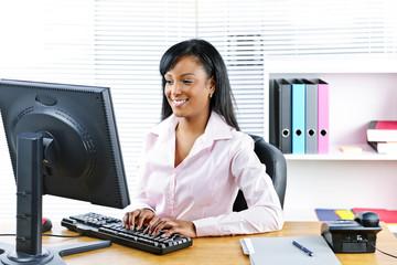 Smiling black businesswoman at desk