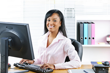 Smiling black businesswoman at desk