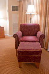 Elegant red armchair and pouffe on carpet