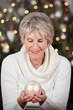 seniorin hält christbaumkugel
