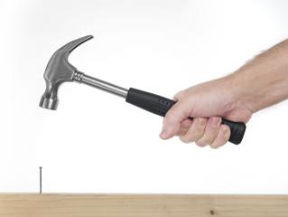 mano di uomo che impugna un  martello