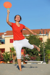 Woman jumps with  tennis racket on beach by sun day