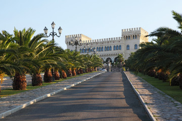 Wide road, which conducts in palace with towers, statues
