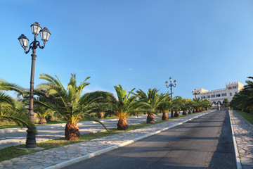 View on palace at end of street with palms and lanterns