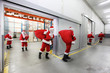 santa clauses leaving a gift distribution center with red sacks