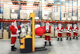 santa clauses in the line for the sacks of gifts in storehouse