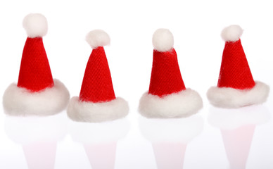 Four small Santa's cap isolated on white with reflection