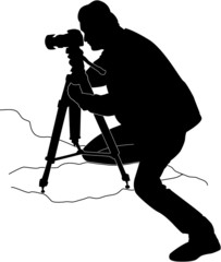 Silhouette of  a half kneeling photographer using a tripod