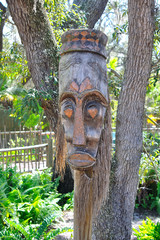 An African mask hanging from a tree at a zoo
